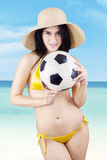 Sexy vrouw die een voetbalbal houden bij strand Stock Afbeelding