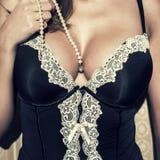 Sexy vrouw die met grote mezen parels houden Royalty-vrije Stock Foto's