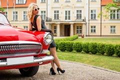 Sexy vrouw die tegen rode uitstekende auto leunen Stock Foto's