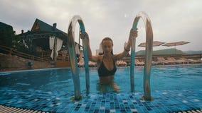 Sexy vrouw die uit de pool in de bergen komen bij zonsondergang HD stock video