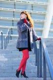 Sexy vrouw in een zwarte kleding, rode legging en een bontjas status stock foto's