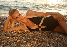 Sexy vrouw in elegant zwempak, die op zonsondergangstrand ontspannen Royalty-vrije Stock Fotografie