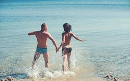 Sexy vrouw en man die in zeewater gaan zwemmen sexy die vrouw en man voor het zwemmen in werking wordt gesteld stock foto