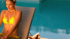 Sexy vrouw in het gele bikini ontspannen op ligstoelpoolside stock footage
