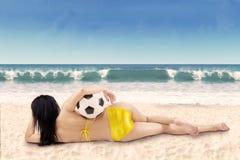 Sexy vrouw met bikini die op strand liggen Stock Foto's