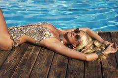 Sexy vrouw met blond haar in elegante zwempak en zonnebril Royalty-vrije Stock Foto's