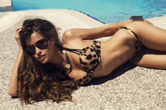 Sexy vrouw met lang haar in bikini het ontspannen naast een zwembad Stock Foto