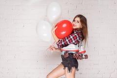 Sexy vrouw met luchtballon en toothy smili van vierlingenrolschaatsen royalty-vrije stock afbeeldingen