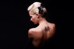 Sexy vrouw met terug tatoegering op haar Royalty-vrije Stock Foto's