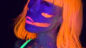 Sexy vrouw met UV fluorescente gezicht en lichaamsmake-up stock footage