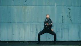 Sexy vrouw, overhemd en beenkappen met mooie moderne samenstelling en haar die tegen blauwe geschilderde bakstenen muur dansen stock video