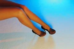 Sexy vrouwelijke benen in hoge hielschoenen tegen veelkleurige texturized achtergrond Stock Foto's