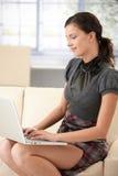 vrouwelijke gebruikende laptop die thuis glimlacht Royalty-vrije Stock Foto's