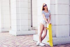 Sexy vrouwelijke tiener die in zonnebril skateboard houden Royalty-vrije Stock Foto's