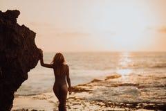 Sexy vrouwen op een tropisch strand in golven overzees, oceaanzonsondergangrotsen op achtergrond stock foto's