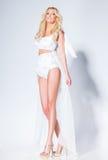 Sexy vrouwenmodel met lange benen gekleed in het witte stellen tegen stock foto