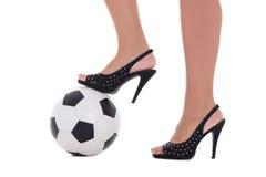 Sexy vrouwenvoeten met hoge hielen en voetbalbal op witte backgro Stock Foto's