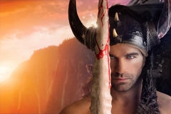 Sexy Warrior Man. Portrait of a beautiful young warrior holding sword with fantasy background Royalty Free Stock Photography