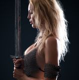 Warrior viking girl with a sword. Beautiful warrior viking girl with a sword in hands on a black background royalty free stock photos