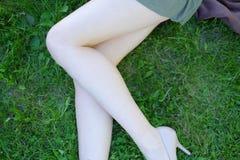 Sexy weibliche Beine auf dem Gras Stockbilder