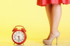weibliche Beine in den hohen Absätzen und in der roten Uhr. Zeit für Weiblichkeit. Lizenzfreies Stockfoto