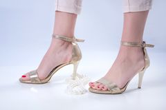 Sexy weibliche Füße in den goldenen Schuhen der hohen Absätze und rote Pediküre auf weißem Hintergrund mit Perlenhalskette lizenzfreie stockbilder