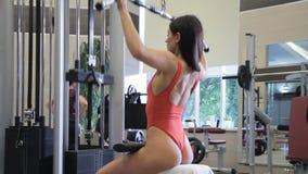Sexy weiblicher Athlet schwingt Muskeln beim Sitzen auf Ausbildungsmaschine stock footage