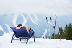 Sexy weiblicher Skifahrer auf blauem Klappstuhl nahe Skis am Skiort Stockfotografie