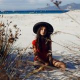 Sexy weibliches Modell, das auf dem Strand auf Sand im roten Badeanzug mit schwarzem Hut, mit geschlossenen Augen, auf einem Meer stockbild