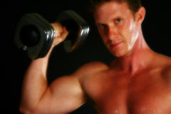 Sexy Weight Lifter. Attractive thirty something man with dumbbell over black Stock Image