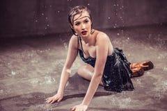 Sexy Wet Girl. Sexy wet brunette girl wears black top sensually lying on water floor Royalty Free Stock Image