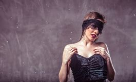 Sexy Wet Girl. Sexy wet brunette girl wears black mask and top under rain drops on grey background with copyspace Royalty Free Stock Image