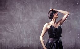 Sexy Wet Girl. Sexy wet brunette girl wears black mask and top under rain drops on grey background with copyspace Stock Photo