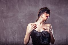 Sexy Wet Girl. Sexy wet brunette girl wears black mask and top under rain drops on grey background with copyspace Stock Images