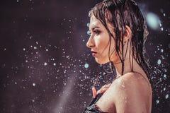 Sexy Wet Girl. Portrait of sexy wet brunette girl wears black top under rain splashes Royalty Free Stock Photo