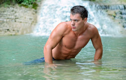 Sexy wet naked young muscular man lying in the water on the background of a waterfall Royalty Free Stock Image