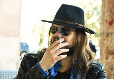 White man with sunglasses and a fedora hat smoking a cigarette. White man with a fedora hat looking like a cowboy smocking a cigarette in a cafe royalty free stock images