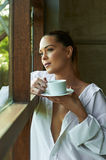 Sexy white shirt window looking out coffee tea cup view beauti Stock Photo