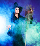 Sexy witch. Sexy young brunette witch with a broom stretching her hand to us, against purple background Stock Photos