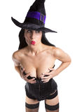 Sexy witch. A sexy witch in a black corset, stockings and hat on white background Royalty Free Stock Images