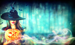 Witch with a Halloween pumpkin Jack-o-lantern. In a dark forest royalty free stock photo