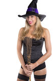 Sexy witch and her broomstick. Royalty Free Stock Photos