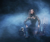 A sexy witch making the witchcraft in the dungeon. Beautiful witch making the witchcraft over the smoky background. Halloween image Royalty Free Stock Photo