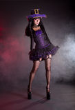 Sexy witch in purple and black gothic Halloween costume. Sexy witch in purple and black gothic fantasy Halloween costume, full length shot Royalty Free Stock Image