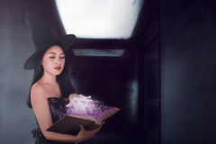 Sexy witch woman spell with the book in the dark room Royalty Free Stock Photography