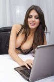 Sexy woma with laptop. A sexy woman lying on the bed with laptop Stock Photos