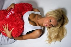 Sexy Woman. A sexy blond woman laying on a white bed holding a red fluffy heart Stock Image