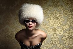 Sexy woman. Portrait of beautiful sexy young woman in white fur hat posing over golden vintage floral wallpaper background Stock Photo