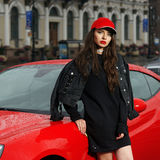 Sexy woman against red sport car Royalty Free Stock Photos