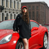 Sexy woman against red sport car Stock Images
